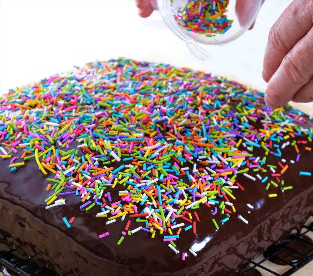 פיזור סוכריות מעל עוגת שוקולד טבעונית